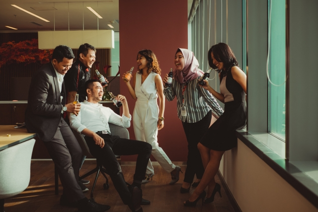 Group of people networking and laughing, man sits in a chair