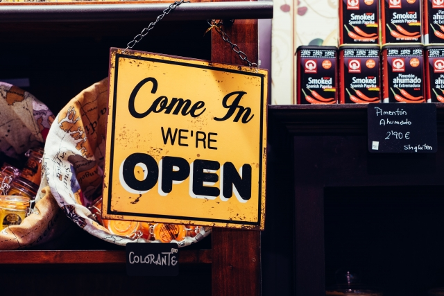 """alvaro serrano image of an old yellow sign that reads """"come in, we're open"""", in black writing."""