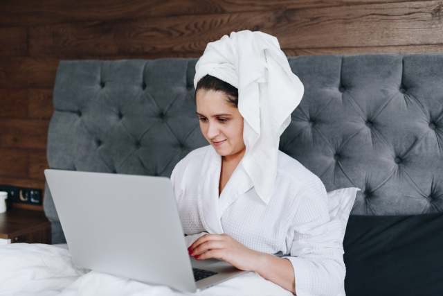 Woman on bed in dressing gown with hair wrapped in towel using her laptop