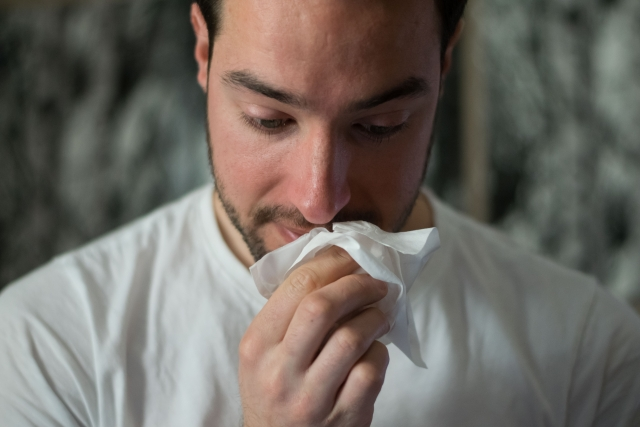 Man in white shirt wiping his nose with tissue feeling unwell