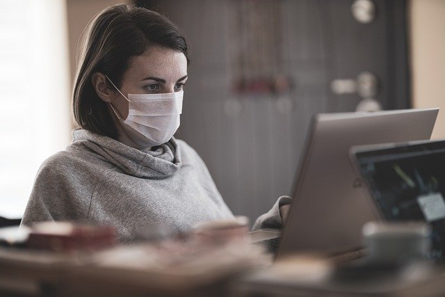 Woman using computer while wearing a mask