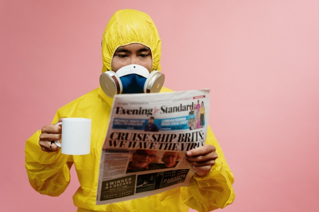 Man in full hazmat suit reading a newspaper and holding a coffee mug.