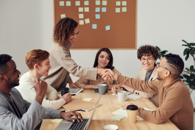 Group at networking event sitting around a table, male and female shake hands.